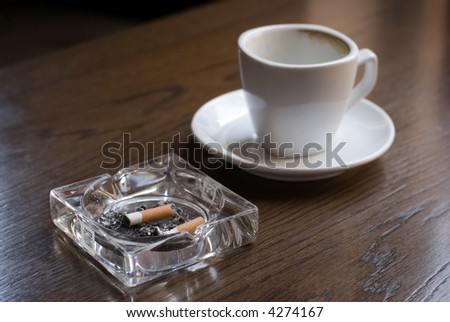 Ashtray and empty coffe cup on the cafe table. Shallow depth of field (focus on the cigarette butt). - stock photo