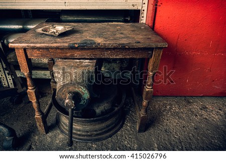 Ashtray on a  grunge wooden table in a junkyard with old mechanical tools