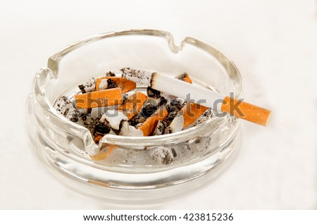 ashtray with cigarette and ash on light background - stock photo