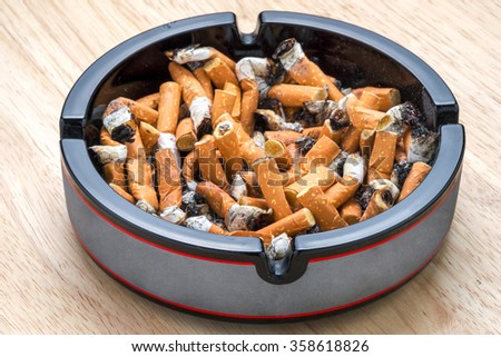 ashtray with cigarette stubs on a wooden table in closeup - stock photo