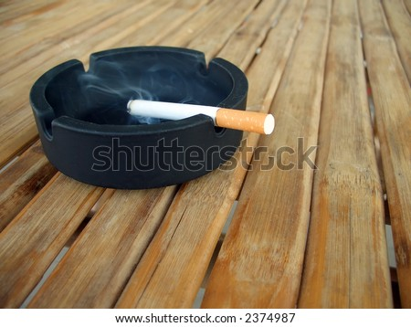 Ashtray with lit cigarette on a wooden table - stock photo
