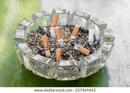 Ashtray with sand ash and crush cigarette butts. - stock photo