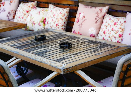 Ashtrays on a table. Ceramic black ashtrays on a wooden table, photographed outdoors on a sunny day - stock photo