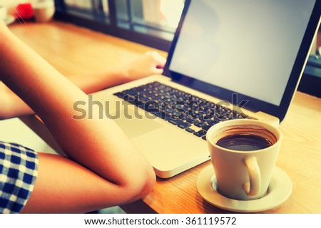 asia beautiful using her laptop and drinking cup of coffee in cafe, Vacations concept. - stock photo