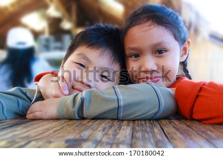 Asia boy and girl smiling sitting in a restaurant. - stock photo