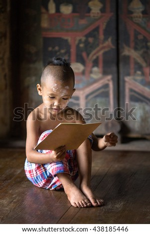 Asia boy reading a book ,the boy sitting on bed wood with traditional Thai suit in Ayutthaya Thailand - stock photo