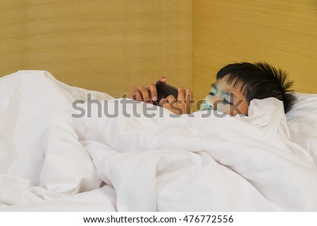Asia boy used smart phone on bed