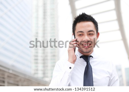 Asia business man using a mobile phone with copyspace - stock photo