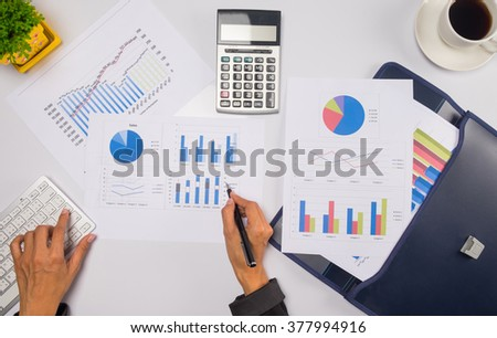 Asia business woman analyzing investment charts on desk.vintage tone Retro filter effect. Top view with soft focus,low light.(selective focus)  - stock photo