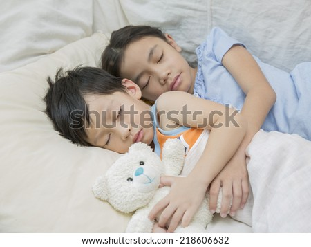 Asia child sleeping with teddy bear - stock photo