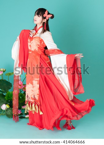 Asia / Chinese girl in red traditional dress sitting on lotus - stock photo