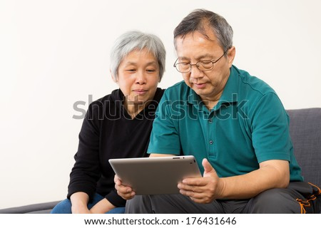 Asia couple using tablet at home - stock photo
