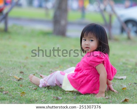 Asia cute little girl is playing with leaves in autumn park - stock photo