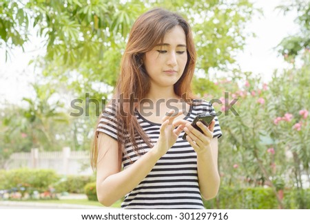asia girl use her smart phone at summer garden