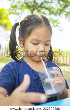Asia little girl is dipping his tongue in the glass of milk