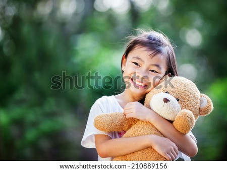 Asia little girl with doll bear in nature park - stock photo