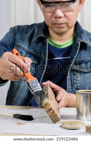 asia man using paintbrush painting wooden plank
