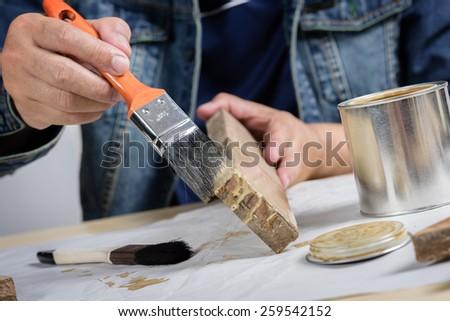 asia man using paintbrush painting wooden plank - stock photo