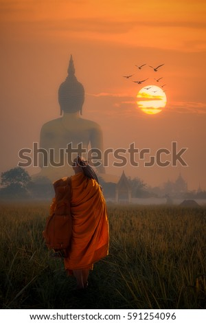 Asia Monk walking behind Big Buddha at Wat Muang Angthong, temple thailand in sunset.