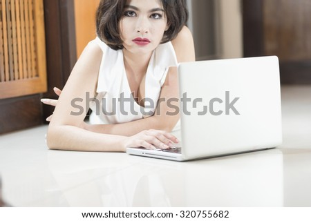 Asia office woman lying on floor with open laptop at home