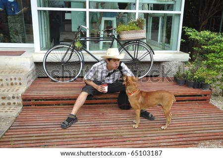 Asia Thailand Man Cowboy Sit With Dog - stock photo