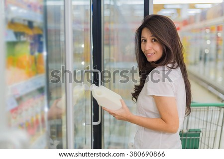 asia woman having on her hands a fresh milk bottle in supermarket.