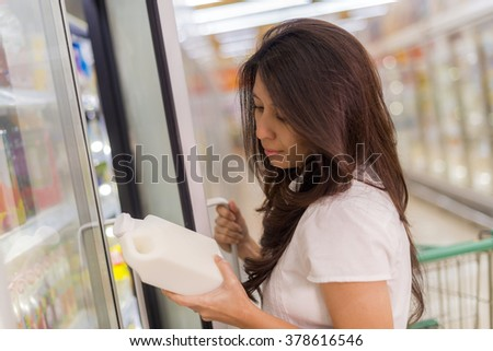 asia woman in a supermarket standing in front of the freezer looking for fresh milk bottle. - stock photo