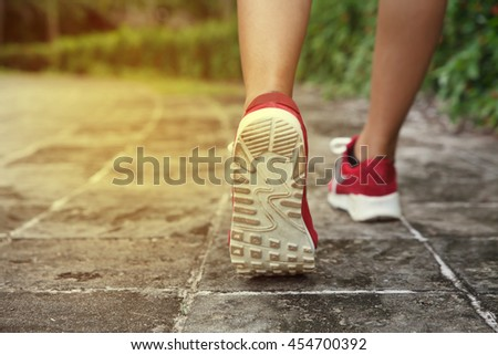 Asia woman running in the park. - stock photo