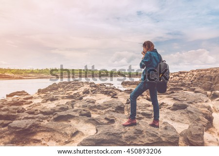 Asia woman taking a photo at Sampanbok natural stone park the grand-canyon of Ubonratchathani Thailand