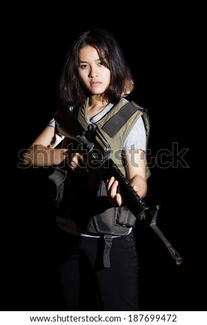 Asia Woman wearing Tactical Gear and Holding a  a rifle. Isolated on black background. - stock photo