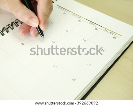 Asia women hand with black pen point on calendar note book. - stock photo