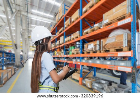 Asia worker women in uniform checking package in modern warehouse - stock photo