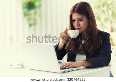 Asia young business woman sitting in a cafe with laptop and coffee, business concept - stock photo
