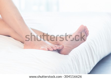 Asia Young woman lying in bed in home with closeup of bare feet - stock photo