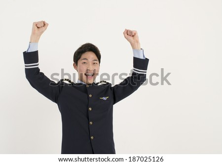 Asian airline pilot holds up his arms  - stock photo