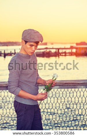Asian American college student seeking love in New York, wearing newsboy cap, knitting sweater, holding white rose, standing by river in sunset, looking down, sad, thinking. Instagram filtered effect. - stock photo