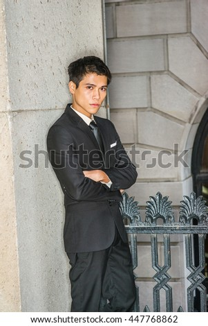 Asian American college student studying in New York. Dressing formally in black suit, neck tie, crossing arms, a businessman standing against wall in corner outside office, taking break, thinking.  - stock photo