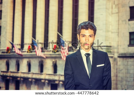 Asian American college student studying in New York. Dressing formally in black suit, neck tie, a young businessman standing in front of vintage office building, looking forward. Retro filtered look.  - stock photo