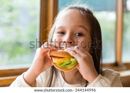 Asian American girl eating burger - stock photo