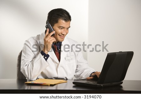 Asian American male doctor sitting at desk with charts and laptop computer talking on cellphone. - stock photo