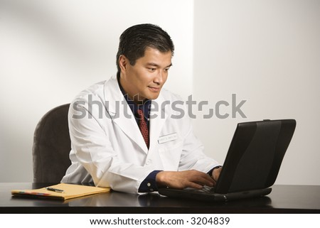 Asian American male doctor sitting at desk with charts typing on  laptop computer. - stock photo