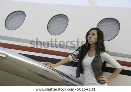 Asian-American woman in her twenties stands leaning on wing of passenger airplane and looking skyward