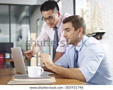 asian and caucasian business executives looking at laptop screen while having a discussion in a multinational company. - stock photo