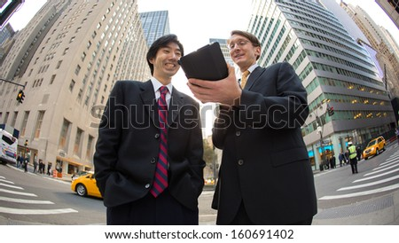 Asian and caucasian businessman in New York City using tablet pc