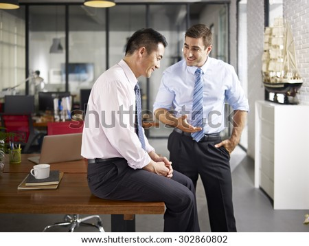 asian and caucasian businessmen enjoying a pleasant conversation in office of a multinational company, focus on the man sitting.  - stock photo