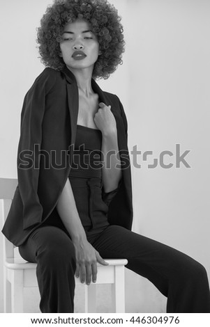 Asian and multi etnic model in studio in high fashion look with curles hair opposit gray background - stock photo