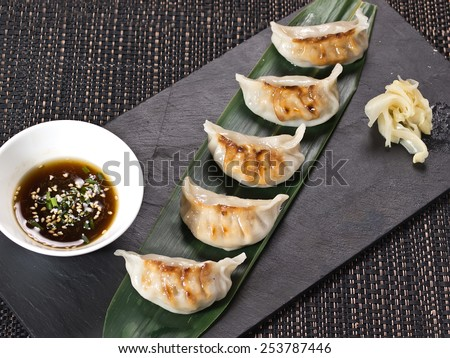 Asian appetizer menu fried dumplings with soy sauce on stone black plate - stock photo