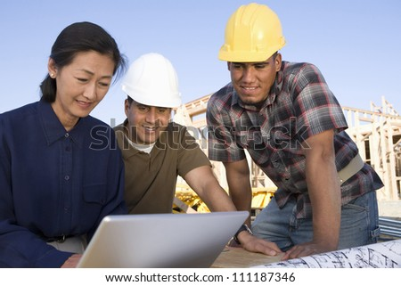 Asian architect with workers using laptop - stock photo