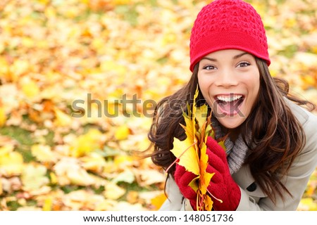 Asian Autumn woman holding fall leaves in forest smiling happy and excited. Cute close up portrait of girl showing colorful leaves outdoor in fall forest foliage. Mixed race Asian Caucasian girl, 20s. - stock photo
