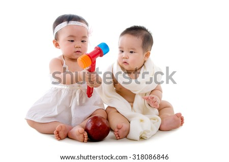 asian babies sitting on the floor playing toys